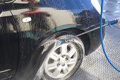 stock photo of pressure-wash  - Washing with pressure gun my new black car - JPG
