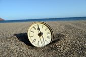 stock photo of analog clock  - Classic Analog Clock In The Sand On The Beach Near The Ocean - JPG