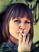 image of teen smoking  - Teenage girl smoking while leaning on a graffiti wall  - JPG
