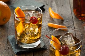 stock photo of orange  - Homemade Old Fashioned Cocktail with Cherries and Orange Peel - JPG