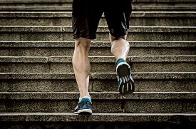 foto of urbanization  - young athletic legs of runner sport man with sharp scarf muscles climbing up city stairs jogging and running in urban training workout our competition in fitness and healthy lifestyle concept - JPG