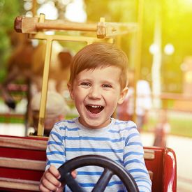 image of merry-go-round  - happy little boy driving a car on merry - JPG