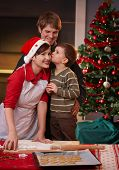 image of nuclear family  - Young boy kissing mum on cheek for baking christmas cake dad watching smiling - JPG