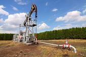 stock photo of nonrenewable  - Grey oil pump jack on field and blue sky - JPG