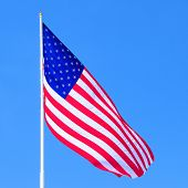 Large US flag with blue sky background