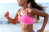 Running Determined Sprinting Woman Runner On Beach. Midsection of sporty woman training on beach. Yo poster