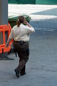 picture of truncheon  - A security guard woman walking and speaking - JPG