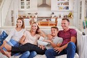 Family With Teenage Children Sitting On Sofa Watching TV Together poster