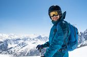 Cheerful skier looking at camera before starting to skiing. Happy man enjoying holiday in winter sea poster