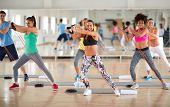 Young group of exercisers doing exercises with resistant rubber in fitness class poster