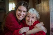 An elderly woman in an embrace with his adult daughter. Positive portrait in the house. poster