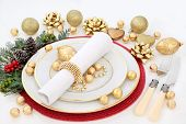 Christmas dinner table setting with porcelain plates, napkin, gold bauble decorations, cutlery, holl poster