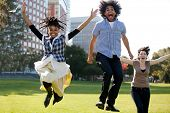 stock photo of black american  - A group of people jumping for joy in a city park - JPG