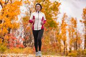 Middle aged mature Asian woman running healthy lifestyle Chinese lady jogging in fall park in her 50 poster