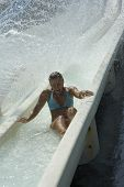 A Young Woman Is Coming Down A Waterslide
