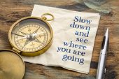 Slow down and see where you are going - inspirational handwriting on a napkin with an antique brass  poster