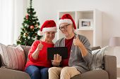 christmas, holidays, communication and people concept - happy smiling senior couple in santa hats wi poster