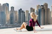 Young woman sits on rooftop of skyscraper in Dubai Marina area in Dubai, UAE poster