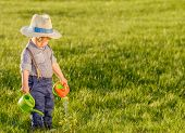 Portrait of toddler child outdoors. Rural scene with one year old baby boy wearing straw hat using w poster