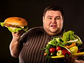 Diet fat man who makes choice between healthy and unhealthy food . Overweight male with hamburgers a poster