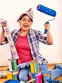 Repair home elderly woman holding paint roller for wallpaper. Happy senior woman in newspaper cap re poster