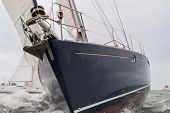 Extreme close up of blue hulled sailing boat, sail boat or yacht at sea with other yachts in the bac poster