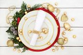 Christmas dinner table setting with porcelain plates, serviette, gold decorations and foil wrapped c poster
