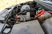Jumper Cables Charging Battery On Car. Red And Black Car Battery Booster Cables. Charging Car Batter poster