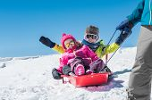 Father sledding his little son and daughter. Cute girl and happy boy being pulled on a red sled. Dad poster