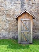 stock photo of outhouses  - Image of a rustic outhouse in front of a vintage stone wall - JPG