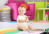 Cute little baby playing with musical instrument at home poster