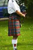 foto of bagpiper  - Scottish bagpiper in full highland dress plays his bagpipes - JPG