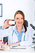 Smiling medical doctor woman sitting at office table and holding blank business card