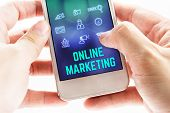 Close Up Two Hand Holding Mobile Phone With Online Marketing Word And Icons On Blurred Blue Backgrou poster
