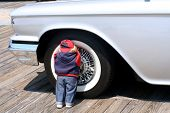 Child Doll Hiding Against Wheel Of Antique Car