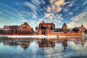 Teutonic castle in Malbork with reflection in frozen Nogat river, Poland