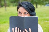 Cheerful Sly Woman Hiding Face Behind Open Diary. Middle Aged Caucasian Lady Reading Notes Outdoors, poster