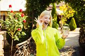 Smiling Girl With Glass Of Water, A Blonde In A Pullover Showing Ok Gesture. Dreamy Girl With Blonde poster