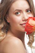 Постер, плакат: Довольно молодая женщина с красивым макияжа и идеально здоровой кожи нюхает розу