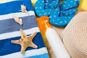 Flip Flops, Straw Hat, Starfish, Sunscreen Bottle, Body Lotion Spray On Yellow Background Top View . poster