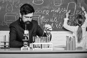 Performing An Experiment. Teacher And Pupil. Male Teacher Giving Lesson In Science Classroom. Public poster