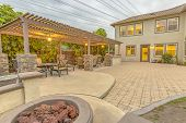 Patio With Dining Area And Built In Circular Benches Wrapped Around A Fire Pit poster
