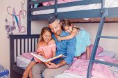 Family Of Three Members People Sitting On Bed In Bedroom Reading Book. Father And Daughters Girls At poster