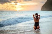 Happy Carefree Woman Enjoying Beautiful Sunset On The Beach poster