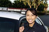 stock photo of lightbar  - A smiling Hispanic police officer next to her patrol car - JPG