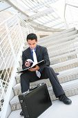 Business Man On Stairs Reviewing Notes