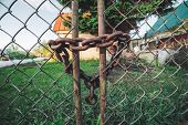 Iron Rusty Chain-link Grid Fence. Rust On Metallic Locked Gate. Chain With Lock Close-up. Grungy Cha poster