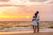 Honeymoon couple walking on sunset romantic stroll on Lovers key beach in Florida enjoying evening  poster