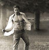 Retrato clássico de homem musculoso ao ar livre, abrindo sua camisa
