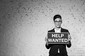 Black and White photo of Portrait of beautiful young businesswoman holding help wanted sign against  poster